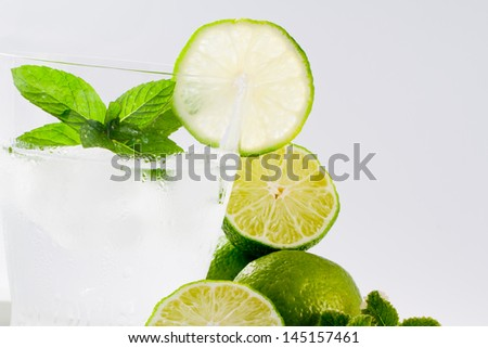Limes, summer refreshing drink - sparkling water with ice and limes, lemonade