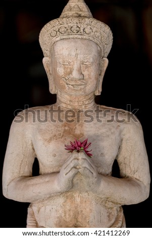 Limestone Buddhist statue with colored flower in hand isolated on back background. Thailand. Selective focus - stock photo