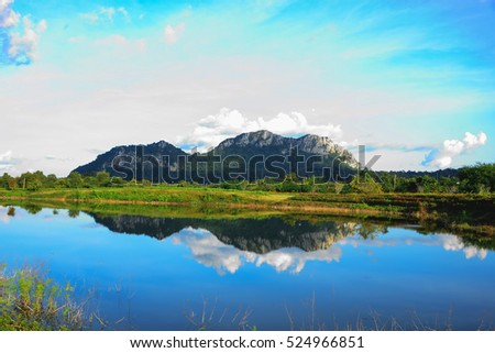 limestone mountain is located in front of a pool of water and sees the reflection in the water is clear.