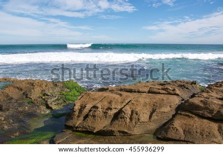 Limestone rock and turquoise Indian Ocean seascape under a blue sky with clouds at Penguin Island in Rockingham, Western Australia/Turquoise Swell/Penguin Island, Rockingham, Western Australia - stock photo