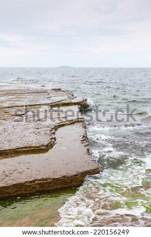 Limestone rock at the shoreline - stock photo
