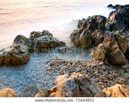 Limestone rocks and pebbles on the shore of the Adriatic Sea, Croatia- - stock photo