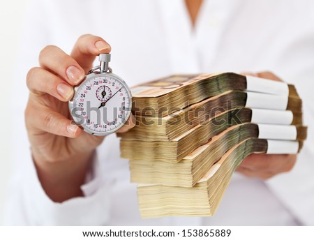 Limited time offer concept with stack of money and stopwatch in woman hands - shallow depth - stock photo