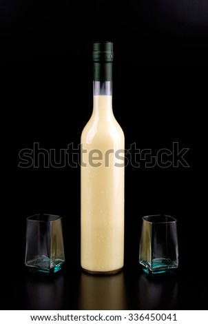Limoncello in bottles with glasses on a black background