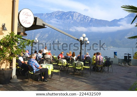 LIMONE,ITALY- OCTOBER 12, 2014: Tourists sitting in cafe nea Garda Lake in Limone town, Italy.Limone is one of the most picturesque towns on the Garda Lake. - stock photo
