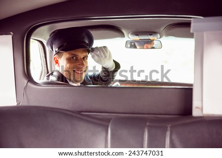 Limousine driver smiling at camera through partition in limousine - stock photo