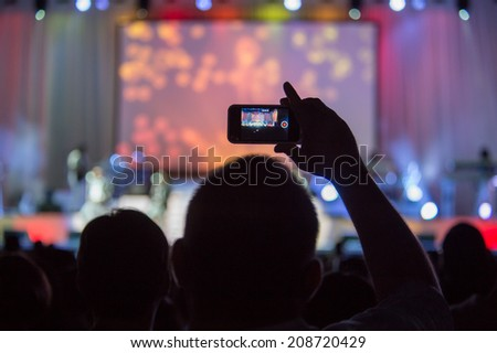 LINCOLN, CA - August 1: Fan records boy band New Edition on a smartphone at Thunder Valley Casino Resort in Lincoln, California on August 1, 2014 - stock photo