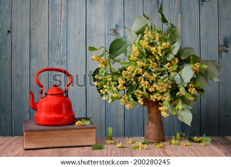 Linden flower in a vase and teapot, book on the table - stock photo
