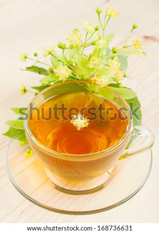 linden flowers and cup of healthy tea, herbal medicine - stock photo