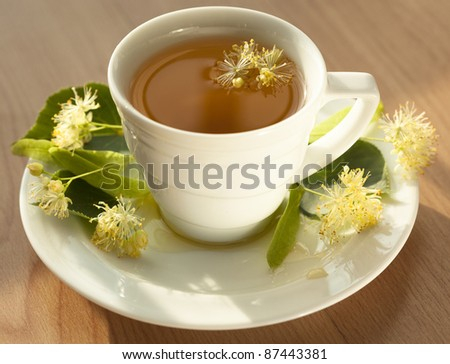 Linden tea in a transparent cup and linden flowers - stock photo