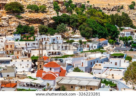 LINDOS, RHODES, GREECE - JUNE 14, 2015: Rooftops view of old Lindos town on the island of Rhodes, popular tourist destination. - stock photo