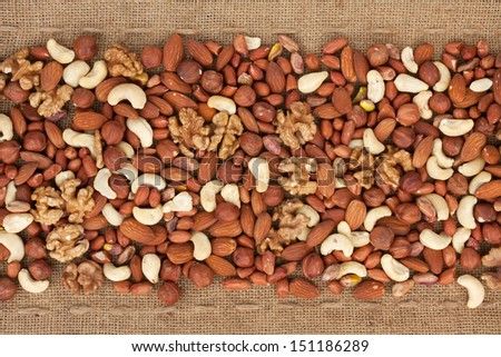 Line,dried nuts  and burlap , can be used as background - stock photo