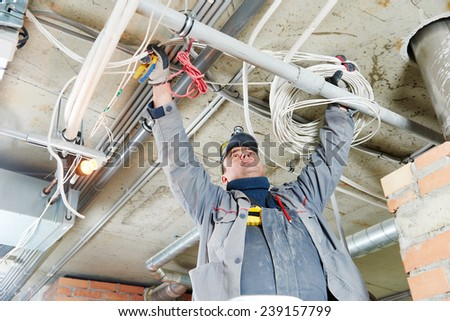 line electrician builder engineer worker at indoor construction site cabling - stock photo