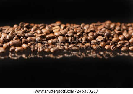 Line of Aromatic Roasted Coffee Beans Placed over Black Background.Horizontal Image Composition - stock photo