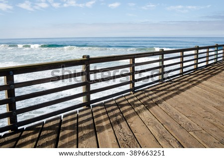 Line of beautiful wooden Pier fence with blue ocean on background - stock photo