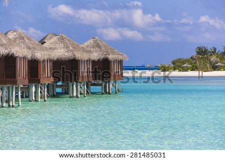 Line of bungalows over a beautiful, clear, turquoise water. It is a beautiful and sunny day with few clouds. At background there is an island with deck chairs and beach umbrella. - stock photo