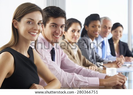 Line Of Business People Listening To Presentation Seated At Glass Boardroom Table - stock photo