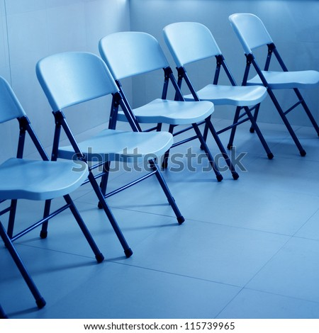 line of chairs in simple empty waiting room. - stock photo
