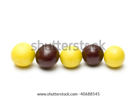Line of chocolate balls and chewing gums isolated on white - stock photo