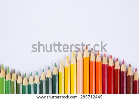 line of colored pencils on white background - stock photo