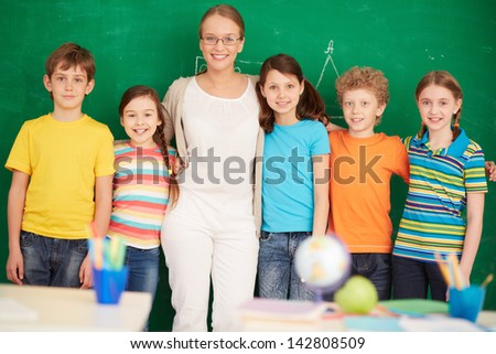 Line of cute schoolchildren looking at camera with their teacher in the middle - stock photo