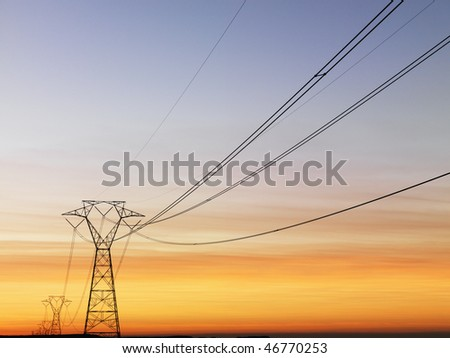 Line of electrical towers and power lines at sunset. Horizontal shot. - stock photo