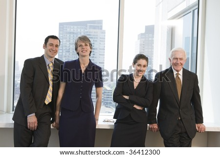Line of four businesspeople smiling and standing at an office window with city view in background. - stock photo