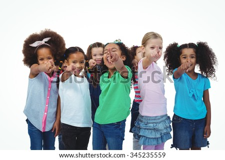 Line of girls standing with hands pointing ahead against a white background