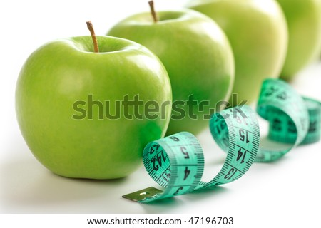 line of green apples and measuring tape