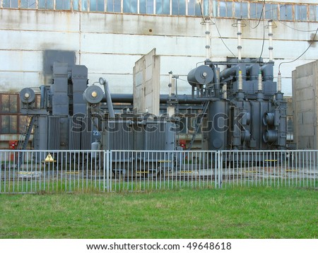 Line of huge high voltage electric converters at a power plant - stock photo