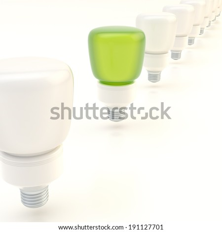 Line of light bulbs over the white surface composition, with the one green bulb standing out - stock photo