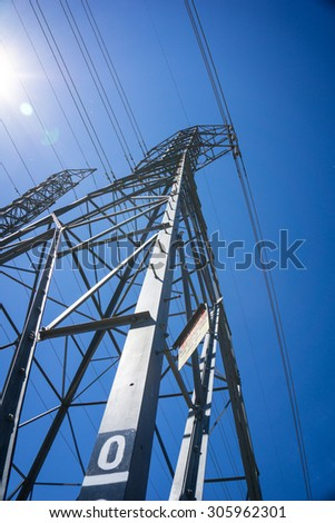 Line of massive metal electric tower structure holding up wires high above the ground. - stock photo