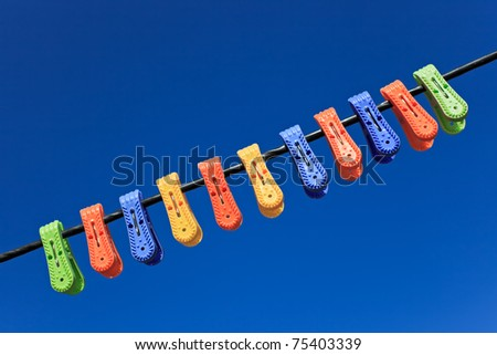 Line of multicolor plastic clothes pegs hanging in front blue sky - stock photo
