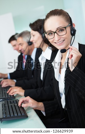 Line of professional stylish call centre operators wearing headsets seated behind their computers giving assistance
