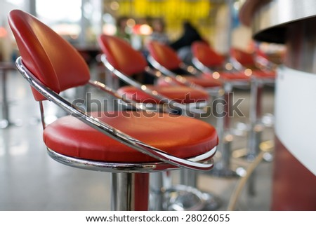 Line of red and chrome diner stools.