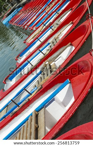 Line of red rowing boats parked at the main pond in the Casa de Campo Park in Madrid, Spain. - stock photo