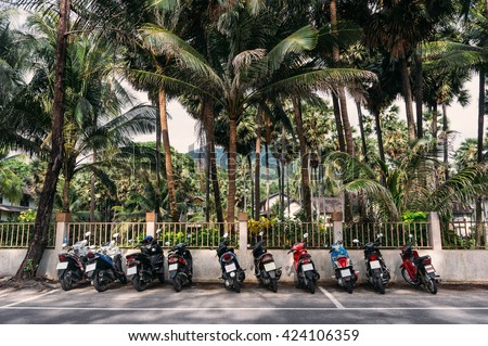 Line of scooters parked on a road near palm trees in Phuket. Thailand. Parked scooters summer view. Thailand scooters. Scooters line in Phuket, Thailand. Urban Phuket - parked scooters at road. - stock photo