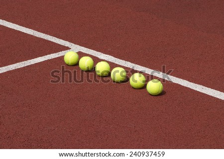 Line of six yellow tennis balls on court with brown synthetic surface closeup - stock photo