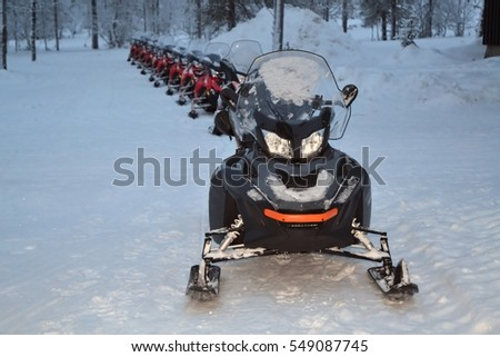 line of snowmobiles in the snow