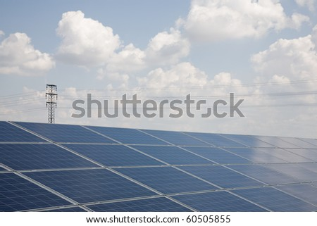 Line of solar power plant panels with clouds and high voltage tower in the background.