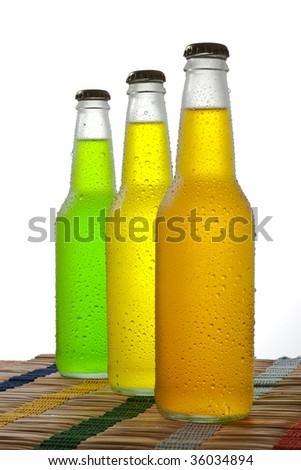 Line of three bottles with tropical drinks on wooden table