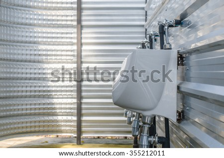 Line of white chamber pot in toilet - stock photo