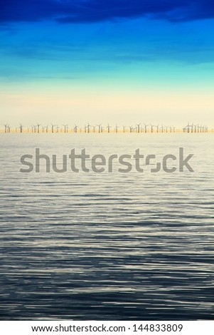 Line of wind energy mills on the coastal horizon/Offshore Wind Farm - stock photo