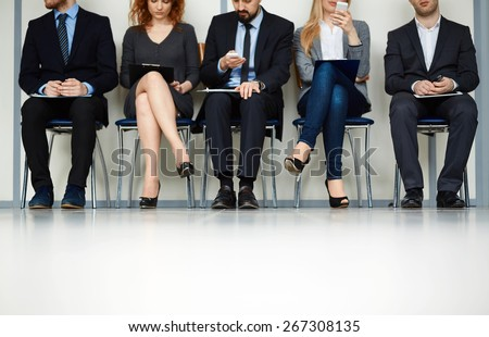 Line of young people sitting by wall while waiting for their turn for interview