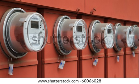 Line up of five electric power meters on red electrical panels