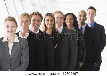 Line up of office staff facing camera - stock photo