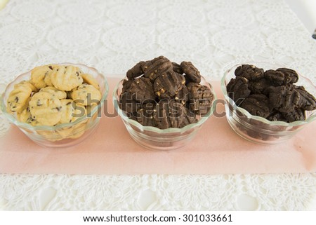 Line up of three varieties of cookies, namely Dark Chocolate Cookies, Milk Chocolate Cookies and Chocolate Chips Cookies.  The cookies are placed in a transparent glass bowl. - stock photo