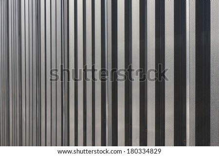 Linear geometric background or texture silvery gray color. Metal structure covered car park facade  - stock photo