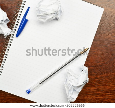 Lined blank copyspace note book lying over the table with the pen and crumpled pieces of paper over it - stock photo