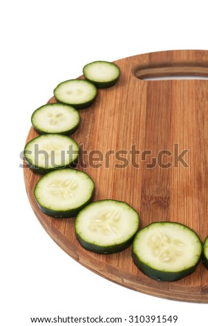 Lined circles of cucumber on a kitchen wooden board.
